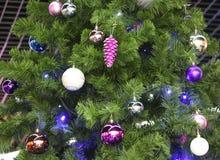 Beaux jouets pourpres brillants sur un arbre velu de nouvelle année Image stock