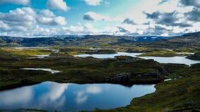 Beaux lacs bleus de glacier reflétant le ciel en parc national norvégien image libre de droits