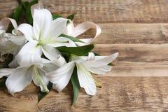 Beaux lis blancs sur la table photographie stock