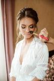 Beaux maquillage et coiffure de mariage de jeune mariée Le styliste fait la jeune mariée de maquillage le jour du mariage photos libres de droits