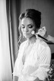 Beaux maquillage et coiffure de mariage de jeune mariée Le styliste fait la jeune mariée de maquillage le jour du mariage photographie stock libre de droits