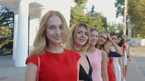 Beaux modèles dans des robes se tenant dans une rangée sur la rue et la pose banque de vidéos