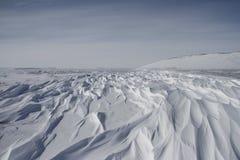 Beaux modèles de sastrugi, arêtes onduleuses parallèles provoquées par des vents sur la surface de la neige dure photographie stock libre de droits