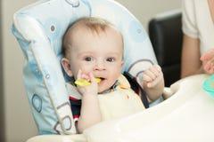 Beaux 9 mois de garçon avec la cuillère se reposant dans le highchair Images stock