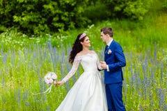 Beaux nouveaux mariés de couples en parc d'été Image libre de droits