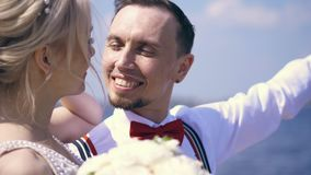 Beaux nouveaux mariés de couples le portrait, le marié regarde dans l'amour la jeune mariée, sourires, contre la mer et le ciel b banque de vidéos