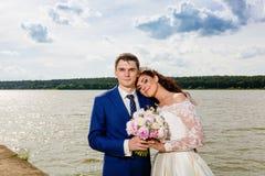 Beaux nouveaux mariés de couples près du lac Photos libres de droits