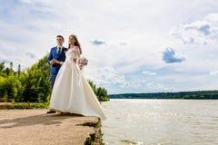 Beaux nouveaux mariés de couples près du lac Image libre de droits