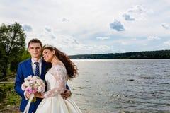 Beaux nouveaux mariés de couples près du lac Photographie stock libre de droits