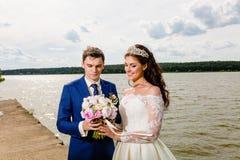 Beaux nouveaux mariés de couples près du lac Photo stock
