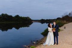 Beaux nouveaux mariés de couples près de la rivière Photos libres de droits