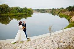 Beaux nouveaux mariés de couples près de la rivière Image stock