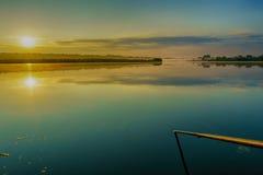 Beaux nuages au-dessus d'un lac au lever de soleil, avec des couleurs brillantes Images stock