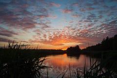 Beaux nuages d'altocumulus de couleur orange près d'un petit lac dans Waddinxveen, Pays-Bas au coucher du soleil photos libres de droits