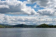 Beaux nuages de pluie au-dessus du lac et du village sur son rivage photographie stock libre de droits