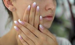 Beaux ongles du ` s de femme avec le bel ombre de manucure française Photos stock