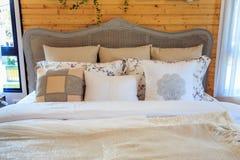 Beaux oreillers sur un lit avec le mur en bois et abat-jour dans le bedroo Image stock