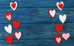 Beaux ornements rouges de coeur sur un fond bleu en bois pour le jour du ` s de Valentine Photographie stock