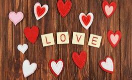 Beaux ornements rouges de coeur sur un fond en bois sur des amants Image stock