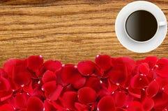Beaux pétales de rose et tasse de café rouges au-dessus de la texture en bois Photos libres de droits