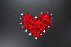 Beaux pétales de rose rouges dans la forme du coeur sur le fond noir Carte postale pour le jour du ` s de Valentine, le 8 mars, j Image libre de droits