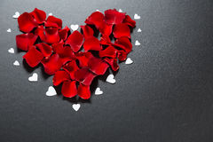 Beaux pétales de rose rouges dans la forme du coeur sur le fond noir Carte postale pour le jour du ` s de Valentine, le 8 mars, j Image stock