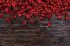 Beaux pétales de rose rouges lumineux sur le fond en bois Concept oliday heureux de ventes de jour de valentines Photo stock