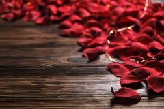 Beaux pétales de rose rouges lumineux sur le fond en bois Concept oliday heureux de ventes de jour de valentines Photos stock