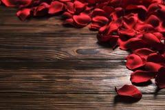 Beaux pétales de rose rouges lumineux sur le fond en bois Concept oliday heureux de ventes de jour de valentines Images stock
