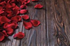 Beaux pétales de rose rouges lumineux sur le fond en bois Concept oliday heureux de ventes de jour de valentines Photos libres de droits