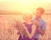 Beaux paysage et couples dans l'amour avec des fleurs sur le coucher du soleil Images stock