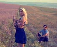 Beaux paysage et couples dans l'amour avec des fleurs sur le coucher du soleil Photos libres de droits