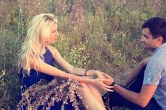 Beaux paysage et couples dans l'amour avec des fleurs sur le coucher du soleil Photos stock