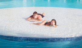 Beaux petite fille joyeuse et adolescent de sourire détendant en île de piscine le beau jour magnifique d'été Image stock