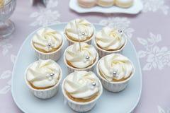 Beaux petits gâteaux savoureux doux décorés multicolores de petit gâteau cuits au four par table de sucrerie sur une partie, banq Photographie stock libre de droits