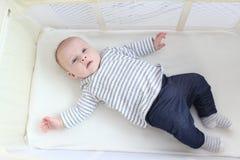 Beaux petits 3 mois de fille se situant dans la huche de voyage Photo stock