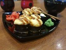 Beaux petits pains savoureux d'un plat noir avec la sauce de soja et les baguettes image stock