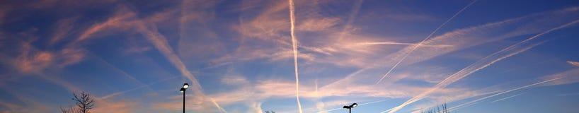 Beaux procès de vapeur des avions pendant un ciel orange de coucher du soleil vu en Allemagne photographie stock