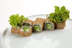 Beaux rouleaux appétissants de sushi d'un plat blanc Photo libre de droits
