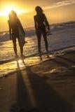 Beaux surfers et planches de surf de femmes de bikini à la plage Image libre de droits