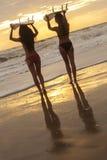 Beaux surfers et planches de surf de femmes de bikini à la plage Photographie stock libre de droits