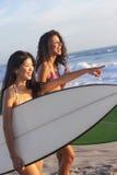 Beaux surfers et planches de surfing de femmes à la plage Photos stock