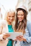 Beaux toursits de filles regardant dans le PC de comprimé Photos stock