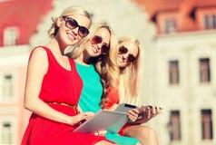 Beaux toursits de filles regardant dans le PC de comprimé Images stock