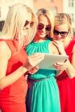 Beaux toursits de filles regardant dans le PC de comprimé Image stock
