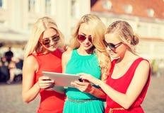 Beaux toursits de filles regardant dans le PC de comprimé Image libre de droits
