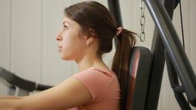 Beaux trains de fille dans le gymnase femme occupée dans un simulateur de sports banque de vidéos