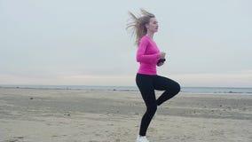 Beaux trains sportifs de fille sur la plage vide et sablonneuse Fonctionnement en place en soulevant vos genoux hauts et en ondul banque de vidéos