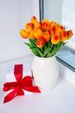Beaux tulipes et boîte-cadeau oranges sur un filon-couche de fenêtre Images stock