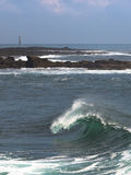 Beaux vague et phare bretons à l'arrière-plan Images stock